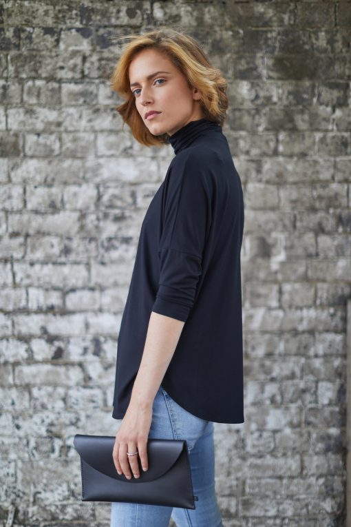 Model waerinf WInster loose fit polo neck top and jeans holding the Derby clutch bag in hand