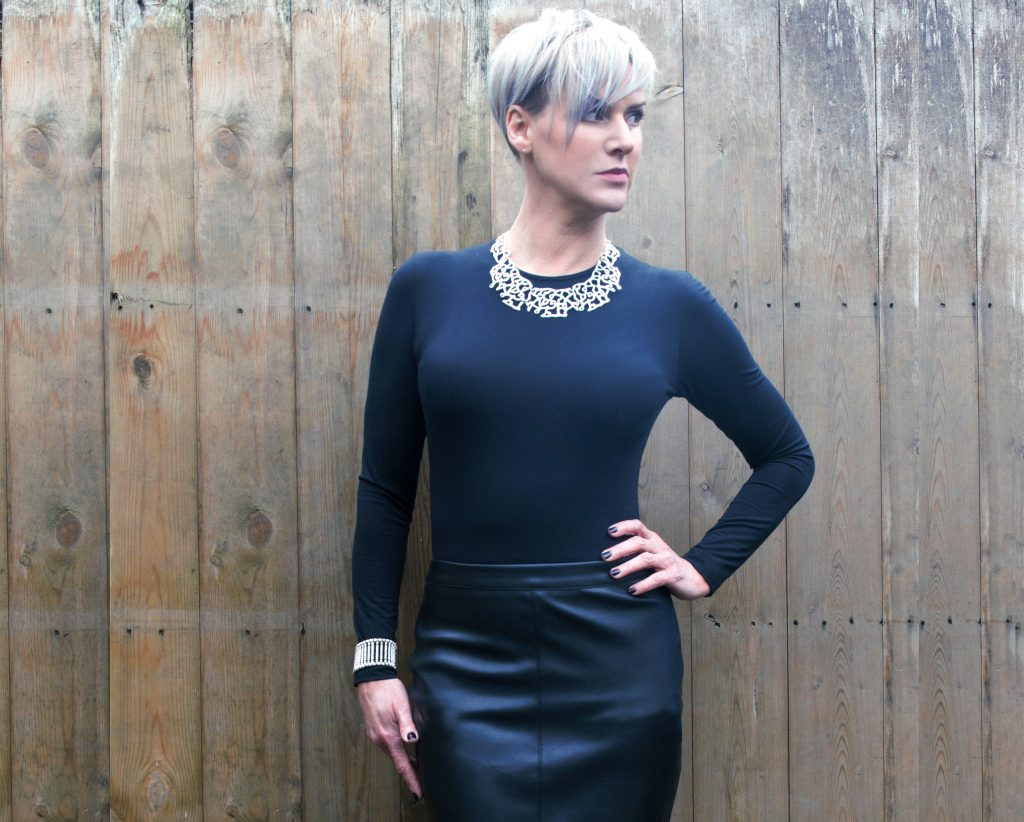 Chester Classic Round Neck Top worn with faux leather skirt and statement jewellery