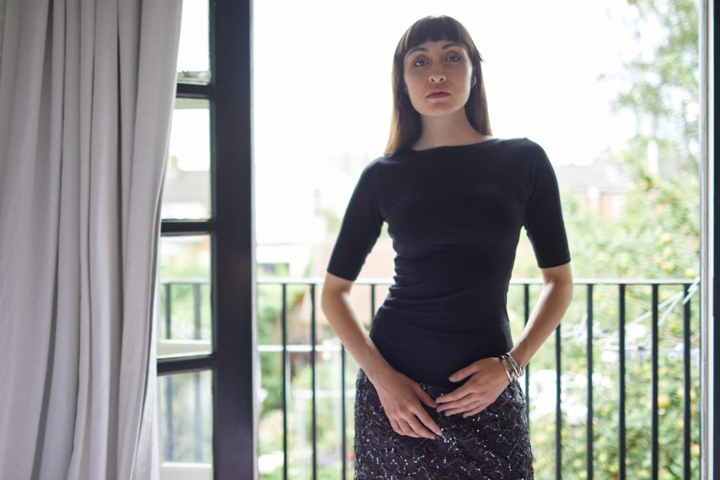 Model stood on a balcony wearing Cambridge Boat Neck and a gray skirt
